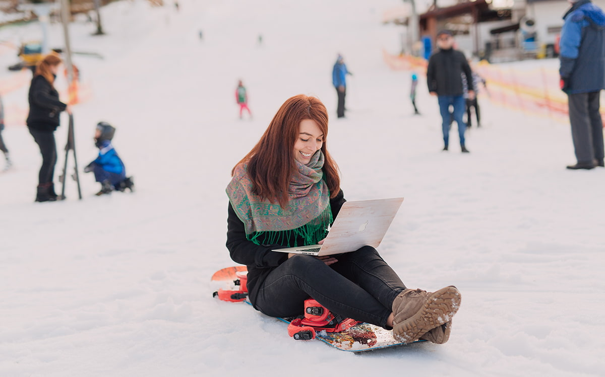 Girl working on her computer on a snowboard